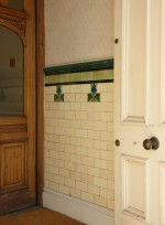 Entrance of Vicarage Chambers with a dado of plain tiles with insets of Art Nouveau tiles